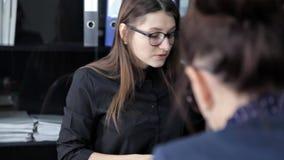 De jonge meisjes zitten in het bureau en bespreken businessplannen en nieuwe projecten stock videobeelden