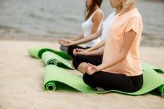 De jonge meisjes zitten in de lotusbloemposities inzake yogamatten op zandig strand op een warme dag stock afbeelding