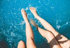 De jonge meisjes zitten op de rand van zwembad en babbelen met hun voeten in het water, bespatten de meisjes hun voeten in de poo royalty-vrije stock afbeeldingen