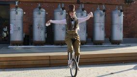 De jonge meisjesclown berijdt een unicycle en jongleert met ballen stock video