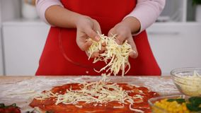 De jonge meisjeshanden bestrooien geraspte kaas op pizza stock footage