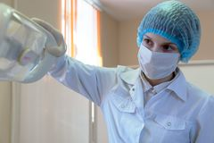 De jonge meisjesmedewerker in een laboratoriumlaag en een beschermende handschoenentandarts past de lamp met het licht aan royalty-vrije stock afbeeldingen