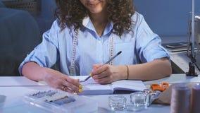De jonge meisjesontwerper die aan een schets van kleren werken en maakt schetsen in notitieboekje stock footage