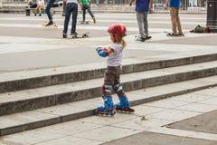 De jonge meisjesschaatser in voorgrond past haar beschermende handschoenen w aan Stock Foto's