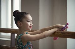 De jonge meisjesturner met clubs kijkt door een groot venster in de zaal voor horeography stock afbeelding