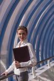 De jonge meisjeszakenman bevindt zich met een omslag op de achtergrond van de vensters van modern commercieel centrum Royalty-vrije Stock Foto