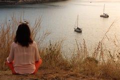 De jonge meisjeszitting in de meditatiepositie van de yogalotusbloem vooraan aan kust op de rotsen het letten op de zon gaat onde Royalty-vrije Stock Foto's