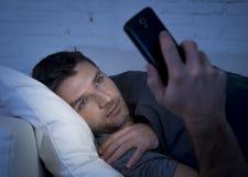 De jonge mens in bedlaag thuis laat bij nacht die mobiele telefoon in laag licht met behulp van ontspande in communicatietechnolo Stock Foto