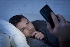 De jonge mens in bedlaag thuis laat bij nacht die mobiele telefoon in laag licht met behulp van ontspande in communicatietechnolo Stock Afbeeldingen
