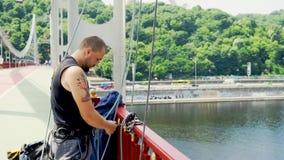 De jonge mens behandelt verzekering voor het springen van de brug stock video