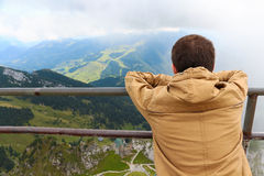 De jonge mens bekijkt de meningszitting op de berg Royalty-vrije Stock Afbeelding