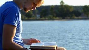 De jonge mens bekijkt een album Een bij vliegt dichtbij op een meerbank stock videobeelden