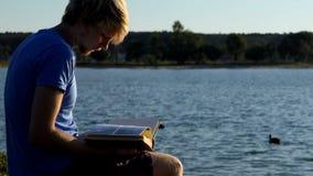 De jonge mens bekijkt foto's De eenden zwemmen dichtbij in een meer stock footage