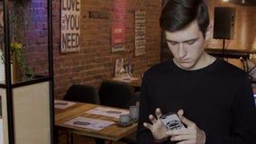 De jonge mens bekijkt het telefoonscherm terwijl status in koffie stock video
