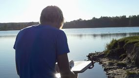 De jonge mens bekijkt zijn familiephotoalbum op een meerbank stock videobeelden