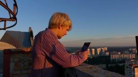 De jonge mens bekijkt zijn mobiel op een hoge bouwwerf bij zonsondergang stock footage