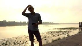 De jonge Mens bekijkt Zijn Smartphone en Dromen in openlucht in Dnipro stock video