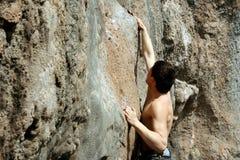 De jonge mens beklimt op een klip over blauwe hemelachtergrond Stock Foto