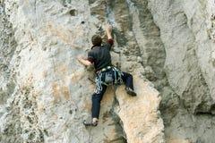 De jonge mens beklimt op een klip over blauwe hemelachtergrond Stock Afbeeldingen