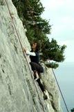 De jonge mens beklimt op een klip over blauwe hemelachtergrond Royalty-vrije Stock Afbeeldingen