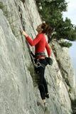 De jonge mens beklimt op een klip over blauwe hemelachtergrond Stock Foto's