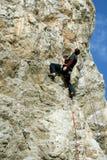 De jonge mens beklimt op een klip over blauwe hemelachtergrond Royalty-vrije Stock Afbeelding