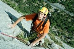 De jonge mens beklimt op een klip over blauwe hemelachtergrond Stock Afbeelding