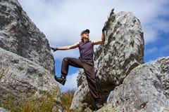 De jonge mens beklimt op rots Royalty-vrije Stock Foto's