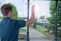De jonge mens bereikt voor een bal van licht royalty-vrije stock afbeeldingen