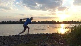 De jonge Mens bevindt zich blootvoets in Water op een Riverbank en werpt een Steen in slo-Mo stock footage