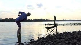 De jonge Mens bevindt zich blootvoets in Water op een Riverbank en werpt een Steen in slo-Mo stock videobeelden