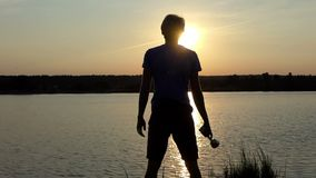 De jonge mens bevindt zich en houdt een winnaarkom bij een meer in slo-mo stock video