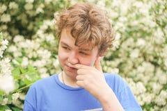 De jonge mens bevindt zich onder de bloemen en geniet van de zomer en het bloeien stock fotografie