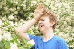 De jonge mens bevindt zich onder de bloemen en geniet van de zomer en het bloeien stock foto's