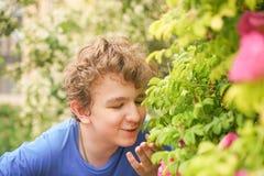 De jonge mens bevindt zich onder de bloemen en geniet van de zomer en het bloeien royalty-vrije stock afbeeldingen