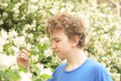 De jonge mens bevindt zich onder de bloemen en geniet van de zomer en het bloeien stock foto