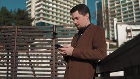 De jonge mens bevindt zich op de straat in de de stadsruimte en drukken sms op een smartphone stock videobeelden