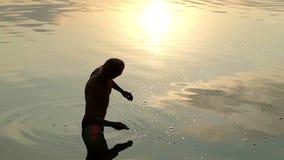 De jonge Mens bevindt zich in Rivierwater en werpt een Vlakke Steen bij Zonsondergang stock videobeelden