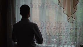 De jonge mens bewondert mening thuis van venster en zette op een overhemd Langzame Motie stock video