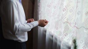 De jonge mens bewondert mening thuis van venster en zette op een overhemd Langzame Motie stock videobeelden
