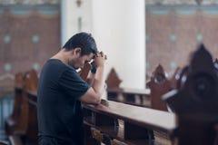 De jonge mens bidt met clasped indient kerk stock foto