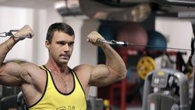 De jonge mens bij de gymnastiek leidt zijn reusachtige wapenspieren op stock videobeelden