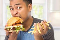 De jonge mens bijt heerlijk zijn grote hamburger Stock Foto