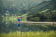 De jonge mens in blauw sweatshirt bevindt zich op pijler door het vulkanische meer stock foto's