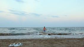 De jonge mens in blauwe uitsmelting gaat in blauw zeewater van camerastrand stock videobeelden