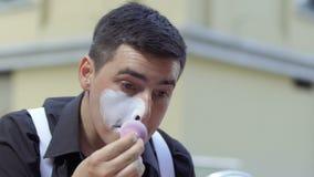 De jonge mens bootst het toepassen van witte verf op zijn gezicht na stock videobeelden
