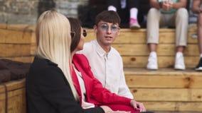 De jonge mens communiceert met twee meisjes stock video