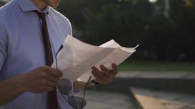 De jonge mens controleert zijn documenten die op de straat bevinden zich stock video