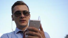 De jonge mens controleert zijn telefoon die op de straat bevinden zich stock videobeelden