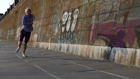 De jonge Mens danst Disco op een Riverbank met een Hoge Steenmuur in de Zomer in slo-Mo stock video